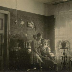 """Abi Šlapelių dukros saulėtą dieną nusifotografavusios savo namų svetainėje. Iš kairės – Gražutė, ant kėdės sėdi Laimutė. Už mėnesio ji ištekės už Kazio Graužinio ir visiems laikams paliks tėvų namus. Kitoje pusėje juodu rašalu užrašyta: """"Dvi sesutės / Vilnius / Mūsų apartamentuose / 1929-VII""""."""