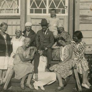 """1928-ųjų liepą Šlapelienė su visais savo vaikais ir kitais giminaičiais ilsėjosi Palangoje. Prie Žaliosios vilos: iš dešinės pirma sėdi Gražutė, šalia jos – sesuo Laimutė, virš kurios, padėjusi ranką dukrai ant sprando sėdi Marija Šlapelienė. Pačiame viršuje stovi sūnus Skaistutis. Kitoje nuotraukos pusėje juodu rašalu užrašyta: """"Prie Žaliosios vilos / Palanga / 1928-VII-25d.""""."""