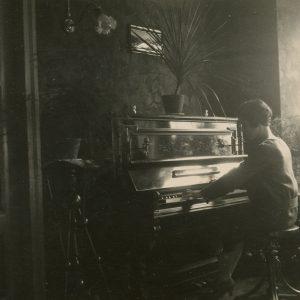 """Gražutė namuose Vilniuje, Pilies g., skambina savo mamos įsigytu pianinu. Kitoje pusėje užrašyta: """"Skambinu … / Vilnius, 1928-X-21d."""""""