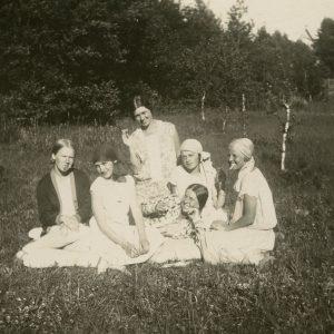"""Šešios merginos Palangoje pievoje, prie jauno beržynėlio. Gražutė guli viduryje, Laimutė – klūpi pačiame viršuje. Kitoje pusėje juodu rašalu užrašyta: """"Mergičkos berūkančios… Tik ne papierosus, o """"Rūtos"""" """"Dūdeles""""… / Palanga. 1928-VII-25d.""""."""